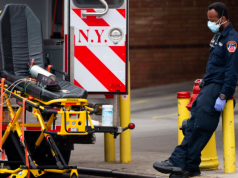 A healthcare worker takes a break outside Wyckoff Heights Medical Center