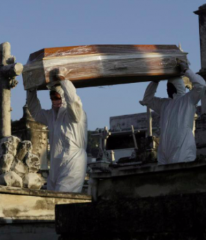 Gravediggers carry the coffin of Antonia Rodrigues during her funeral who passed away from the coronavirus disease