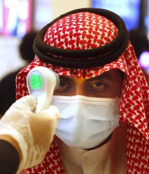 A Saudi cinema viewer has his temperature taken as he wears a face mask to help curb the spread of the coronavirus,