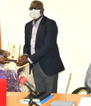 Permanent Secretary, Special Duties Office, Temitope Fashedemi presents a plaque to Dr Ibrahim Bashir, Head, Public Health Department, State House Clinic, in recognition of his exemplary contributions to the COVID-19 response in the State House. With them is Permanent Secretary, State House, Tijjani Umar.