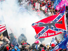 Tear gas is released into a crowd of protesters, with one wielding a Confederate battle flag