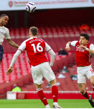 Man City's Raheem Sterling jumps to head home the opening goal against Arsenal