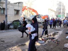 People walk past debris in a street at the site of Israeli air strikes, in Gaza City